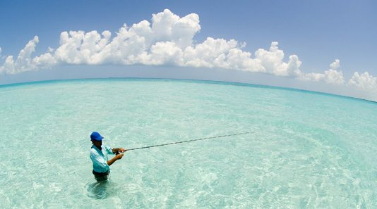 Fly fisherman casting for Bonefish in emerald green water