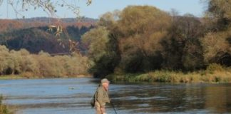 Fly fisherman Lawrence Greasley contemplates the island water at Zaluz on the San River in Poland.